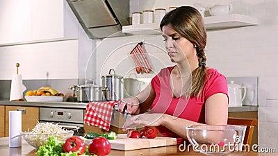 Mujer adulta corta un tomate para una ensalada de verduras almacen de video