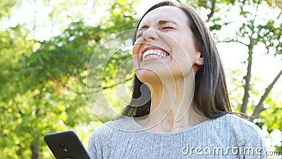 Mujer adulta emocionada que comprueba el teléfono elegante