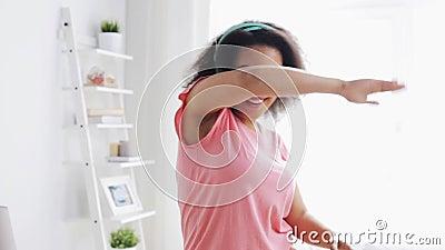 Mujer africana feliz en los auriculares que bailan en casa