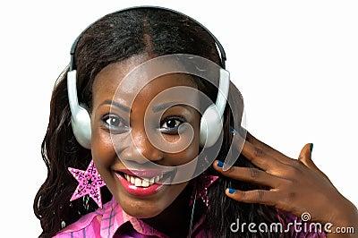 Mujer afroamericana feliz que escucha la música con el auricular