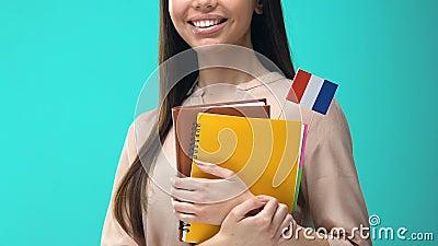 Mujer alegre con cuadernos de bandera francesa, programa educativo internacional almacen de metraje de vídeo