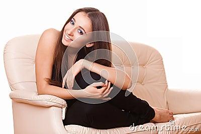 Mujer alegre que se sienta en el sofá