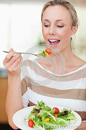 Mujer alrededor para comer un poco de ensalada