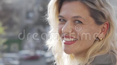 Mujer amablemente madura sonriendo a la cámara sobre su hombro metrajes
