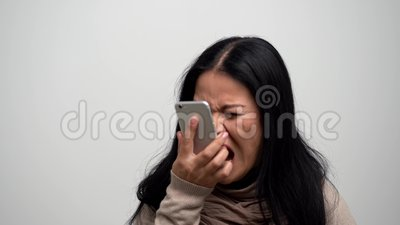 Mujer asiática enojada que grita en su teléfono metrajes