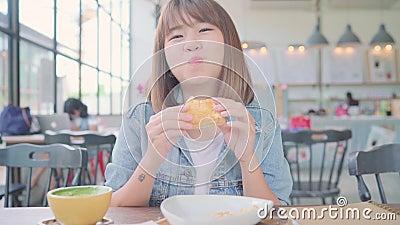 Mujer asiática que trabaja como independiente comiendo pan y tomando una taza de café caliente mientras se sienta en la mesa en  almacen de metraje de vídeo