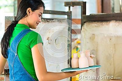 Mujer asiática con cerámica hecha a mano