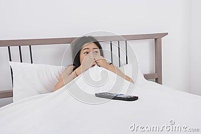 Mujer asustada que ve la TV en cama