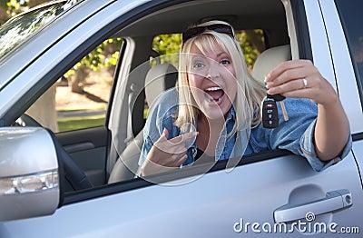 Mujer atractiva en nuevo coche con claves