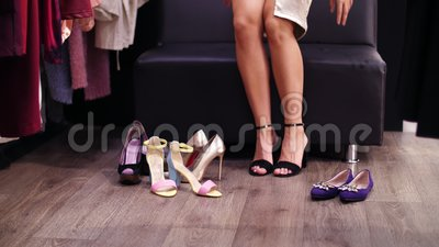 Mujer atractiva, zanquilarga que intenta en las sandalias de tacón alto negras en una tienda elegante, boutique Cámara lenta Prim almacen de video