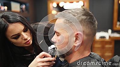 Mujer barbero corta la barba del hombre con un puertazo en la barbería Peluquería masculina y corte de pelo en salón Crecer el metrajes