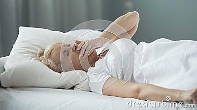 Mujer bastante rubia que despierta, estirando las manos y bostezando, buena mañana metrajes