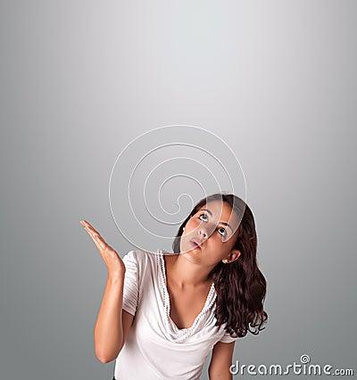 Mujer bonita que gesticula con el espacio de la copia