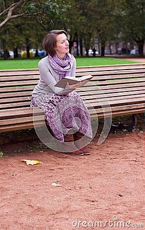 Mujer bonita que lee un libro en banco y el pensamiento