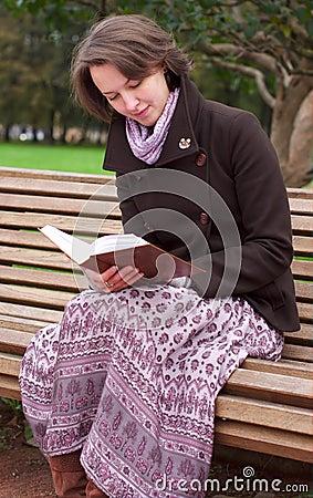 Mujer bonita que lee un libro en un banco