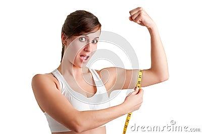 Mujer chocada que mide su bíceps