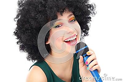 Mujer con el micrófono que se sostiene afro