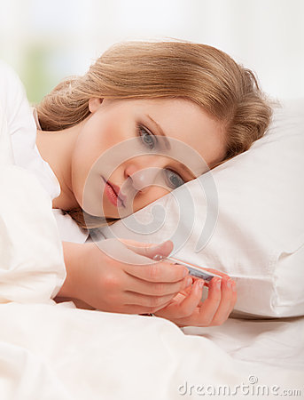 Mujer con fríos enfermos del termómetro, gripe, fiebre en cama