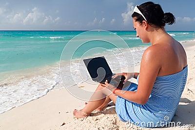 Mujer con la computadora portátil en el mar del Caribe