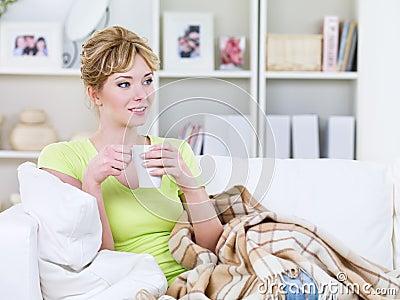 Mujer con la taza de bebida que se calienta