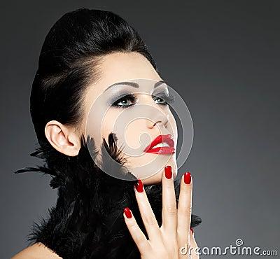 Mujer con los clavos rojos y el peinado creativo
