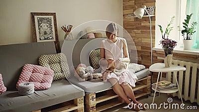 Mujer creativa que se sienta en el sofá y la ropa de lana que hace punto almacen de metraje de vídeo