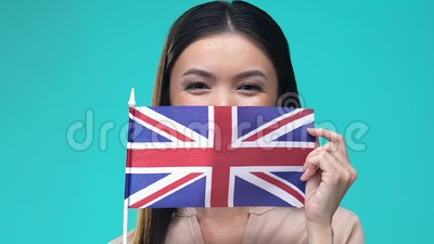Mujer cubriendo la boca bandera británica, cultura nacional, educación en el extranjero, migración almacen de video
