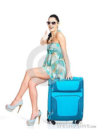 Mujer de ?asual que se coloca con la maleta del viaje