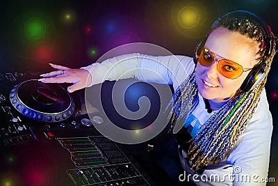 Mujer de DJ que juega música por el mikser