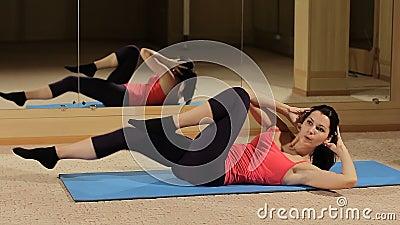 Mujer de la aptitud para hacer crujidos abdominales Modelo apto que hace crujidos abdominales y que golpea sus piernas con el pie metrajes