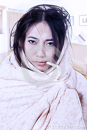 Mujer de la fiebre con el termómetro envuelto en manta