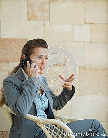 Mujer de negocios en cuestión que habla el teléfono móvil