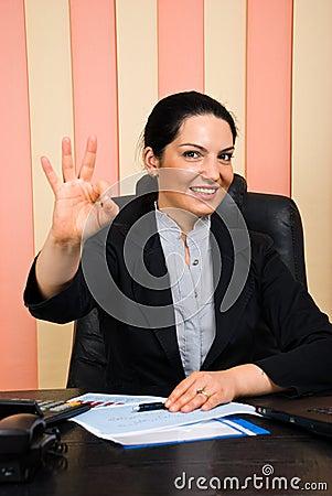 Mujer de negocios feliz que muestra la mano aceptable de la muestra