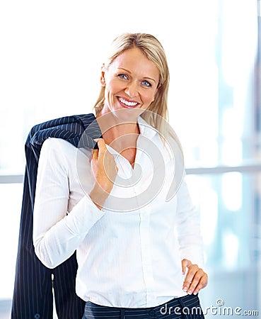 Mujer de negocios linda que presenta con su capa