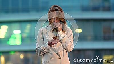 Mujer de negocios mirando el teléfono móvil en la ciudad por la noche almacen de metraje de vídeo