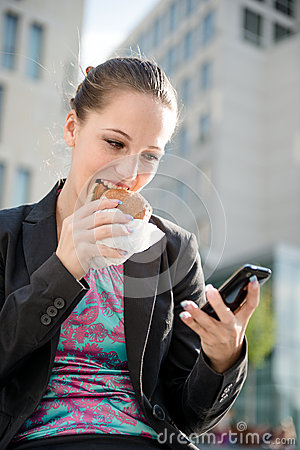 Mujer de negocios que come y que trabaja con el teléfono