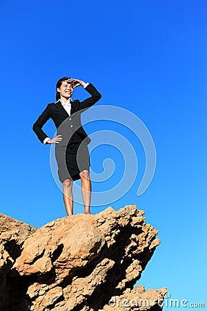 Mujer de negocios que mira de tapa de la montaña