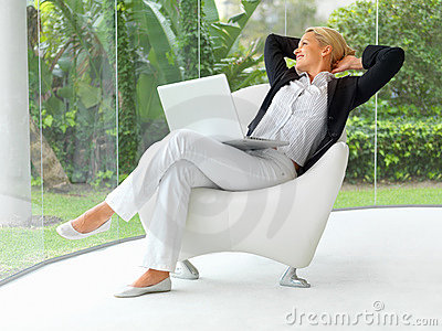 Mujer de negocios que se sienta en una silla con la computadora portátil
