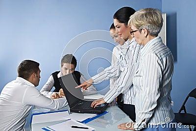 Mujer de negocios que señala a la computadora portátil en la reunión