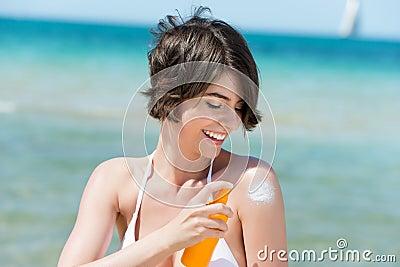 Mujer de risa que aplica la loción del bronceado
