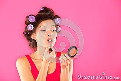Mujer del maquillaje que pone el lápiz labial