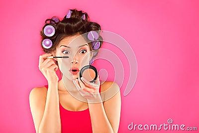 Mujer del rimel del maquillaje con los rodillos del pelo