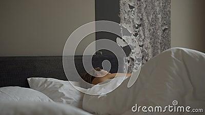 Mujer despierta por la mañana y toma el smartphone a la vez Una mujer se despierta en la mañana en la cama y toma el smartphone e metrajes