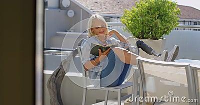 Mujer discapacitada que lee un libro en el balcón 4k almacen de metraje de vídeo