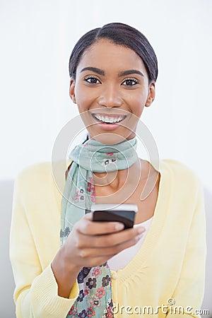 Mujer elegante alegre que se sienta en envío de mensajes de texto del sofá