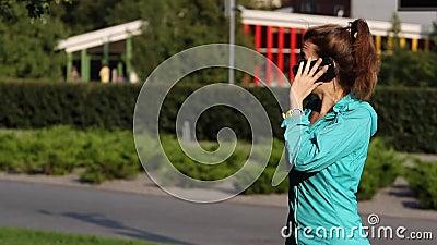 Mujer elegante del teléfono que invita al teléfono móvil en el parque Mujer joven hermosa que habla en la sonrisa del smartphone  almacen de metraje de vídeo