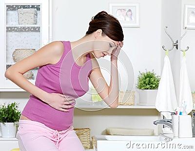 Mujer embarazada con el dolor fuerte del estómago