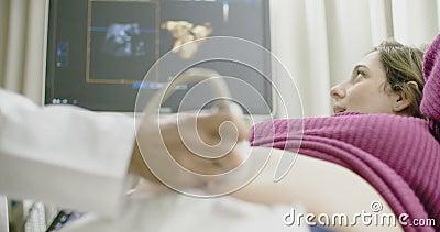Mujer embarazada durante una exploración del ultrasonido del bebé almacen de video