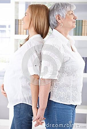 Mujer embarazada y madre que se colocan adosadas mutuamente