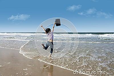 Mujer emocionada con la computadora portátil en la playa